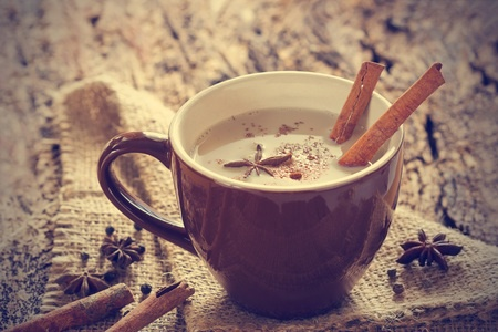 45295723 - masala chai tea with spices and star anise, cinnamon stick, peppercorns, on sack and wooden background