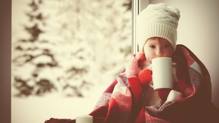 46429451 - child little girl sitting by the window with a cup of hot tea and looking at the winter forest